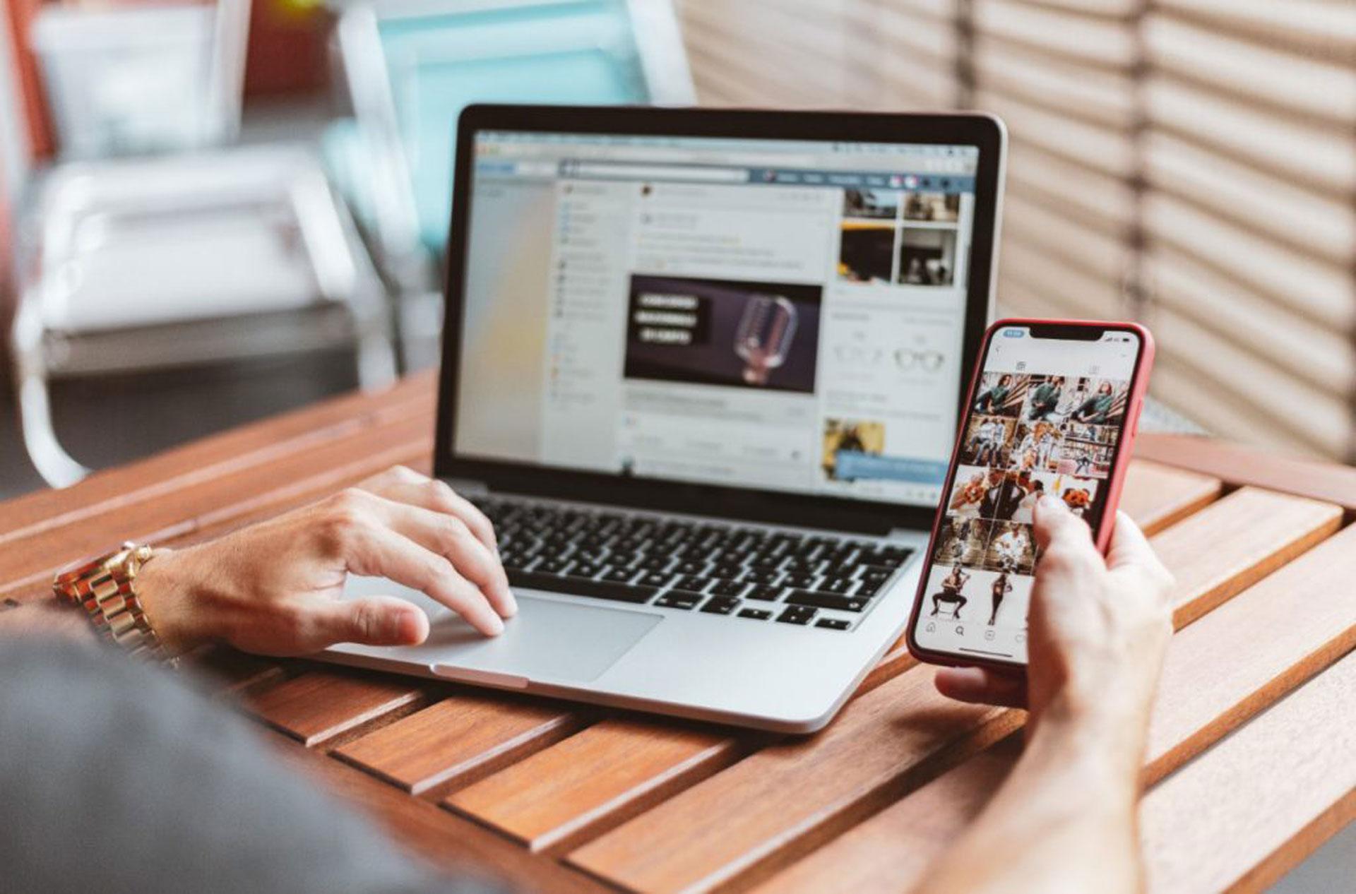 homme consulte réseaux sociaux sur son téléphone et sur son ordinateur